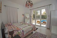 Inredesign av sovrummet i lyxig villa med trädgårds- sikt royaltyfria bilder