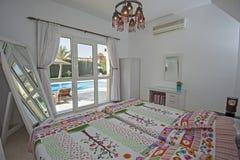 Inredesign av sovrummet i villa med den trädgårds- simbassängen VI royaltyfri bild