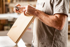 Inredningssnickare som mäter med hans klämma Arkivbild