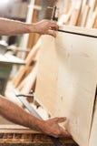 Inredningssnickarehänder med träbrädet arkivfoto