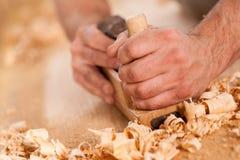 Inredningssnickarehänder som rakar med en nivå royaltyfria bilder