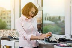 Inreformgivare, på arbetsplatsen med prövkopior av tyger och tillbehör för gardiner och stoppning Royaltyfri Bild