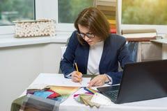 Inreformgivare, på arbetsplatsen med prövkopior av tyger och tillbehör för gardiner och stoppning Arkivbilder
