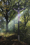 INRI cross. Beam of light through the trees at the cross with Jesus Stock Images