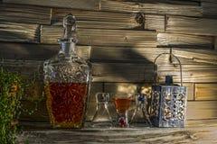 Inristad flaska med whisky, exponeringsglas och stearinljuset royaltyfri fotografi