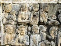 Inristade diagram visar berättelsen av Buddha på en stenvägg av Borobudur, Indonesien Royaltyfri Bild