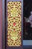 Inristade guld- blommor på träfönster i tempel Fotografering för Bildbyråer