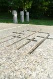 Inristade kors i en marmorplatta på kyrkogård Arkivfoto