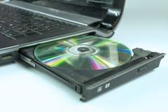 Insérez un CD dans l'ordinateur portable photos stock