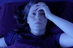Insônia acordada da noite da cama da mulher Foto de Stock Royalty Free