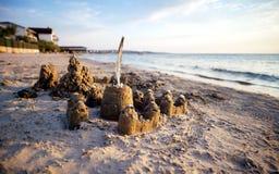 Insabbi il castello sulla spiaggia con gli ornamenti fatti delle coperture Immagini Stock