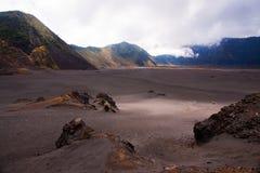 Insabbi il mare con le montagne ai precedenti e ad un cielo appannato Fotografia Stock