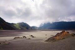 Insabbi il mare con le montagne ai precedenti e ad un cielo appannato Immagine Stock