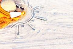 Insabbi la struttura con il cappello, l'asciugamano, la protezione solare e gli occhiali da sole su una spiaggia Fotografie Stock