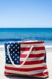 Insacchi con i colori della bandiera americana vicino all'oceano sulla spiaggia sabbiosa Fotografie Stock Libere da Diritti