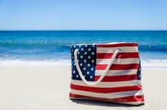 Insacchi con i colori della bandiera americana vicino all'oceano sulla spiaggia sabbiosa Immagini Stock Libere da Diritti