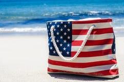 Insacchi con i colori della bandiera americana vicino all'oceano sulla spiaggia sabbiosa Fotografie Stock
