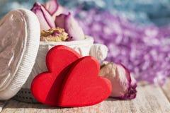 Insacchi fatto a mano con le rose secche e due cuori rossi luminosi Fotografie Stock Libere da Diritti
