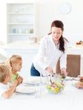 Insalata adorabile del servizio della madre ai suoi bambini immagini stock