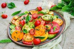 Insalata colorata del pomodoro con la cipolla ed il basilico Alimento del vegano fotografia stock