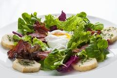 Insalata con bacon e l'uovo affogato su un piatto bianco fotografia stock