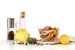 Insalata con gli ortaggi freschi in ciotola e olio d'oliva di vetro, spezie ed erbe Immagine Stock Libera da Diritti