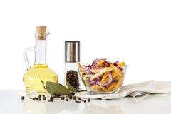 Insalata con gli ortaggi freschi in ciotola e olio d'oliva di vetro, spezie ed erbe Immagini Stock Libere da Diritti