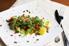 Insalata con gli ortaggi freschi, semi di zucca, arance sul piatto bianco Immagini Stock Libere da Diritti