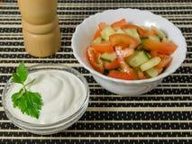 Insalata con i cetrioli e pomodori e panna acida Fotografia Stock