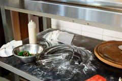 Insalata con i verdi e funghi in una tazza del metallo durante la cottura su un bordo nero nella cucina fotografie stock libere da diritti