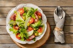 Insalata con il prosciutto arrostito, i pomodori, le mele e le olive verdi Fotografie Stock