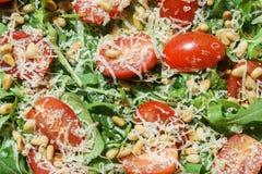 Insalata con la rucola, gli spinaci, i pomodori, il parmigiano ed i pinoli Immagini Stock