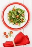 Insalata con la rucola, i pomodori ciliegia e la mozzarella su bianco e Fotografia Stock