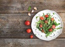 Insalata con la rucola, i pomodori ciliegia, i semi di girasole e le erbe sul piatto ceramico bianco sopra fondo di legno rustico Fotografia Stock Libera da Diritti