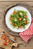 Insalata con la rucola, i pomodori ciliegia, la mozzarella, i pinoli e la b Fotografie Stock