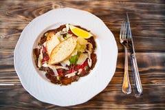 Insalata con le fette di carne e di verdure affumicate su un piatto bianco Immagine Stock Libera da Diritti