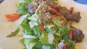 Insalata da fegato in sesamo, basilico e pepe bulgaro, bugia su un'insalata della zucca stock footage