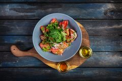 Insalata dal prezzemolo della cipolla dei pomodori e da due generi di olio con i semi di sesamo su un bordo di legno Vista superi Fotografia Stock