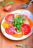 Insalata dei pomodori, della cipolla rossa e della rucola Immagini Stock