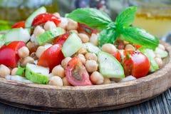 Insalata del cece con i pomodori ciliegia, il cetriolo, il basilico e la cipolla con il condimento dell'agrume, orizzontale, prim Immagini Stock Libere da Diritti