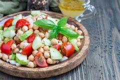 Insalata del cece con i pomodori ciliegia, il cetriolo, il basilico e la cipolla con il condimento dell'agrume, orizzontale, spaz Immagini Stock