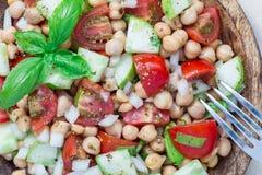 Insalata del cece con i pomodori ciliegia, il cetriolo, il basilico e la cipolla con il condimento dell'agrume, orizzontale, vist Immagine Stock