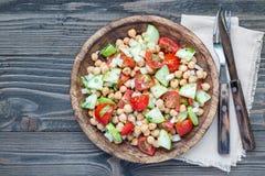 Insalata del cece con i pomodori ciliegia, il cetriolo, il basilico e la cipolla con il condimento dell'agrume, orizzontale, vist Immagini Stock