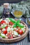 Insalata del cece con i pomodori ciliegia, il cetriolo, il basilico e la cipolla con il condimento dell'agrume, verticale Fotografie Stock