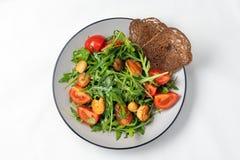 Insalata del pomodoro con i gamberetti, la rucola e la fetta biscottata della segale su un fondo bianco fotografia stock