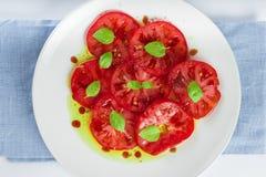 Insalata del pomodoro con le foglie del basilico Fotografia Stock Libera da Diritti
