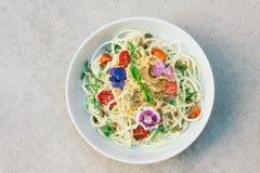Insalata deliziosa con i semi di canapa, spinaci, semi degli spaghetti dello zucchini di zucca, decorati con i fiori, in ciotola, immagine stock libera da diritti