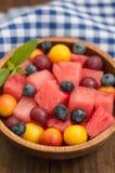 Insalata della bacca e della frutta dell'anguria, mirtilli, prugne, uva passa, uva spina, ciliegia susina Priorità bassa di legno Fotografie Stock Libere da Diritti