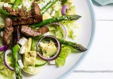 Insalata della striscia della bistecca con l'avocado, l'asparago, la cipolla rossa e la feta ch fotografie stock