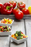 Insalata della verdura fresca in ciotola bianca Tavola del partito della primavera Immagini Stock